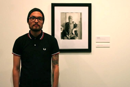 Arthur with a photo of his grandfather, which won a prize at the Vincent Price Art Museum's juried art competition.